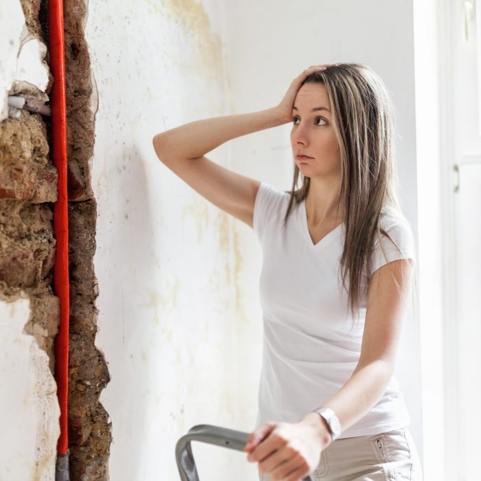 Woman looking at damage after a water pipe leak at home